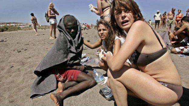 Turistas ayudan a un inmigrante en una playa de las islas Canarias