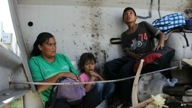 Una mujer migrante con sus hijos en el tren carguero conocido como La Bestia