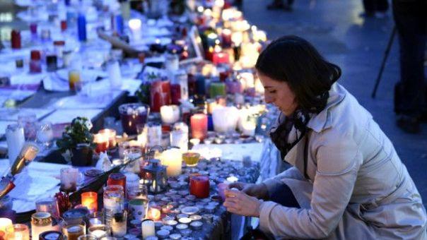 Una mujer enciende una vela en honore a los muertos en los ataques del 13 de noviembre en París.