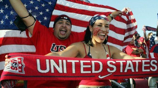 Dos personas sostienen la bandera de Estados Unidos