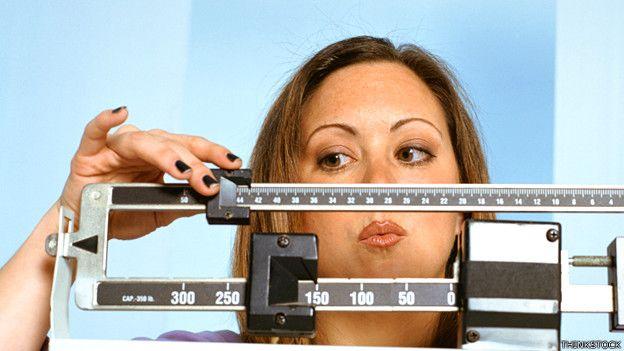 Mujer pesándose en una balanza