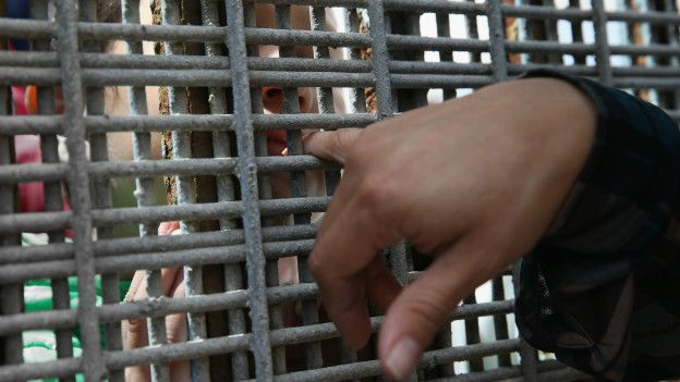 Dos personas se tocan con el dedo entre la valla
