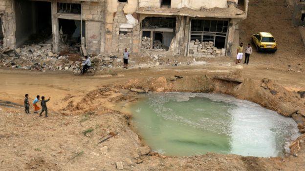 阿勒頗居民察看一處填滿水的受損地帶