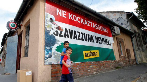布達佩斯街頭兩名小孩走過匈牙利政府宣傳歐盟移民配額公投海報(28/9/2016)