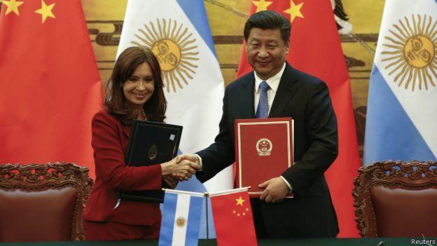 Los presidentes de Argentina y China se estrechan las manos.
