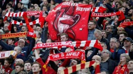 Célébrer les supporters de Liverpool en brandissant des écharpes et des banderoles