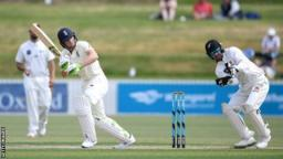 England batsman Jos Buttler plays a shot and New Zealand A wicketkeeper Tom Blundell turns to watch the ball in a warm-up match