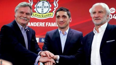 Bayer Leverkusen's new head coach Tayfun Korkut poses for photographers with chief executive Michael Schade and sports director Rudi Voller