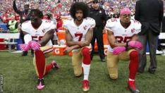 Eli Harold, Colin Kaepernick and Eric Reid kneeling in protest during the American national anthem