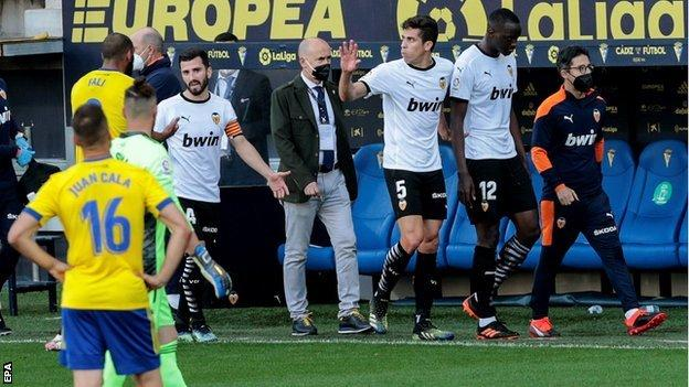 Valencia's Mouctar Diakhaby leaves the field after alleging Juan Cala (r) racially abused him
