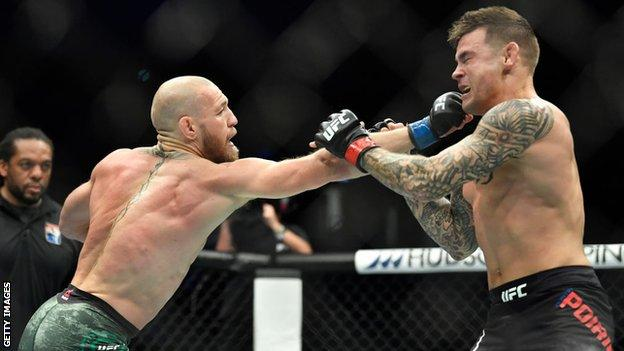 Conor McGregor punches Dustin Poirier during their rematch at UFC 257