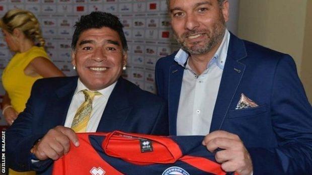 Diego Maradona with Guillem Balague holding up a Biggleswade United shirt