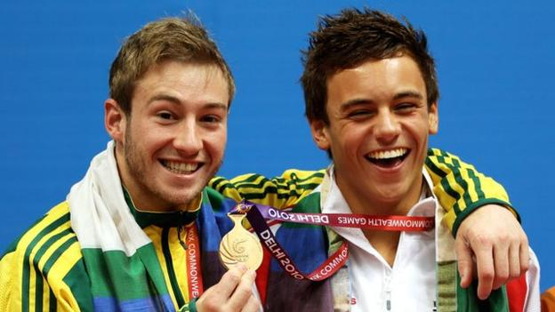 Divers Matthew Mitcham (left) and Tom Daley (right) smiling as Mitcham holds up Daley's 2010 Commonwealth Games gold medal