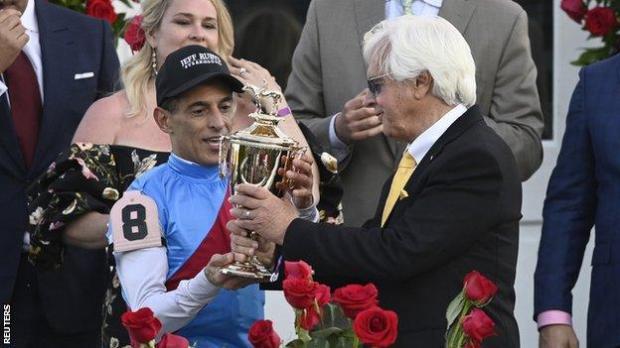 Jockey John Velazquez (left) and trainer Bob Baffert (right) hold up the trophy after Medina Spirit won the 2021 Kentucky Derby
