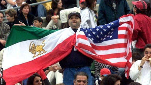 A man holds up the flags of Iran (the flag in use up to the revolution of 1979) and the United States at the 2000 friendly match between the nations