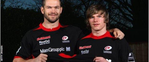 Andy Farrell has his arm round a young Owen Farrell and both are holding a Saracens shirt with Farrell on the back