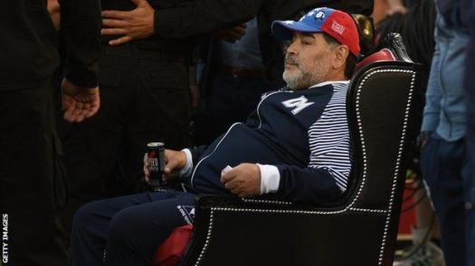 Maradona sits in a throne presented to him