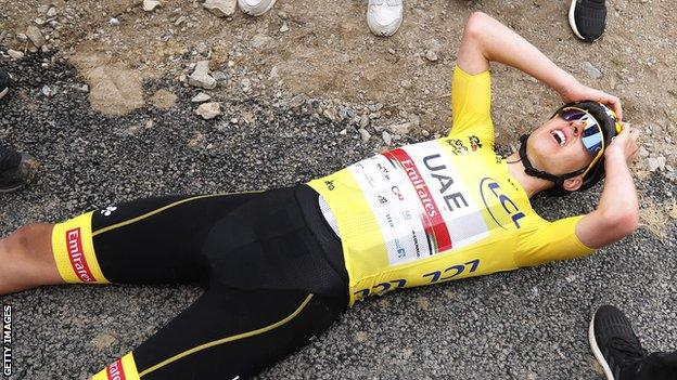 Yellow jersey wearer Tadej Pogacar lies on the floor in exhaustion after winning stage 17 of the 2021 Tour de France