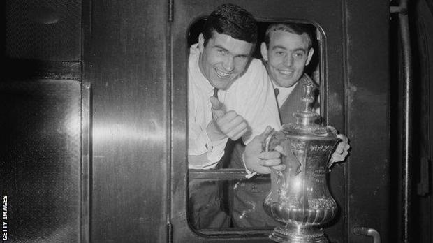 Liverpool captain Ron Yeats (left) St John show off the 1965 FA Cup trophy from the train that will take them from Euston back to Liverpool