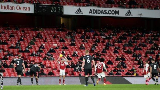 Socially distanced fans at Emirates Stadium watch Arsenal against Burnley