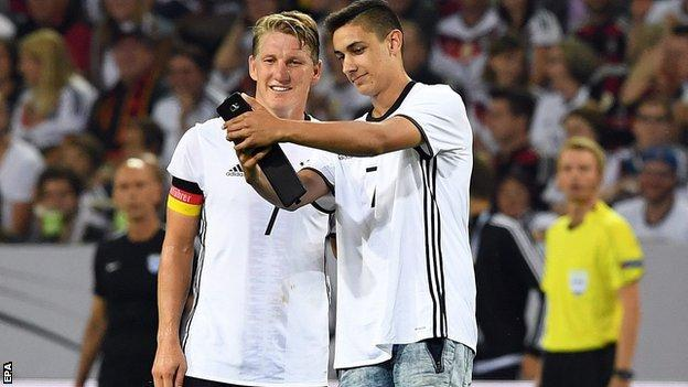 A pitch invader gets a selfie with the departing Germany legend