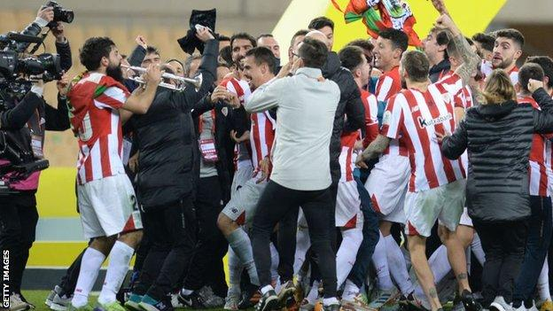 Asier Villalibre plays a trumpet as Athletic Bilbao celebrate after beating Barcelona