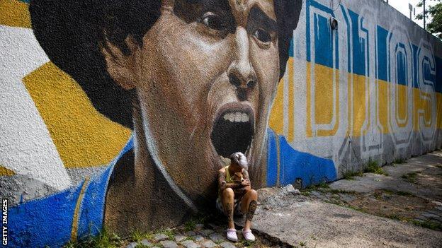 Boca Juniors women's player Yamila Rodriguez cries in front of graffiti image of Diego Maradona