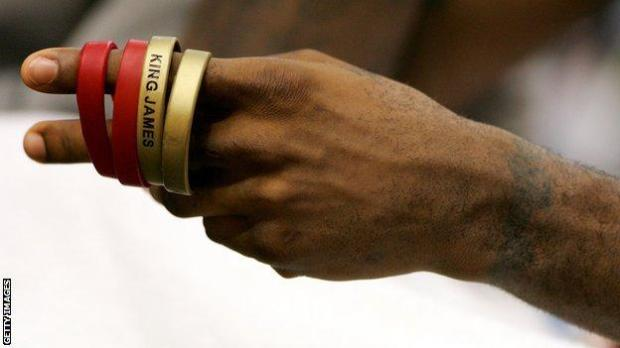 LeBron James plays with his 'King James' wrist bands as he sits on the bench against the Portland Trail Blazers on 17 January, 2006