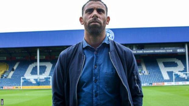 Anton Ferdinand stands on the pitch at Loftus Road