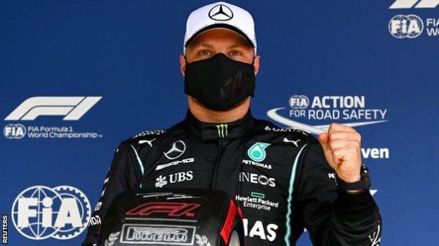 Valtteri Bottas holds up his pole position tyre