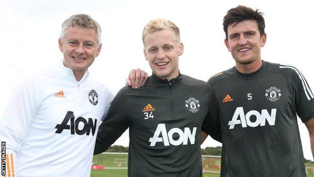 Donny van de Beek poses with Manchester United manager Ole Gunnar Solskjaer and captain Harry Maguire