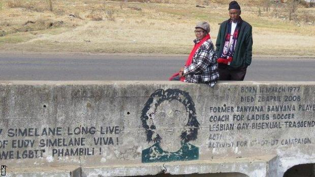 Eudy Simelane's mother Mally (left) and father Khotso (right) sit on the bridge built in honour of their murdered daughter next to a mural of her face on the wall