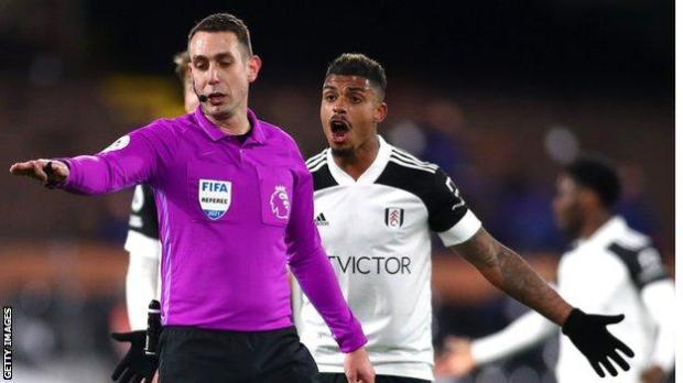 David Coote pauses for a VAR review as Mario Lemina appeals
