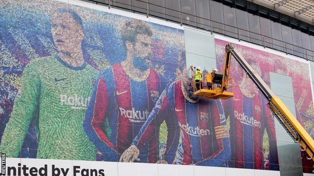 A picture of Lionel Messi is taken down outside the Nou Camp