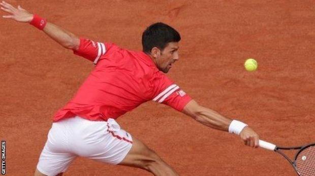 Novak Djokovic stretches for a ball against Ricardas Berankis