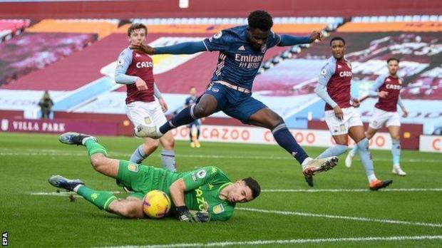 Aston Villa keeper Emiliano Martinez in action against Arsenal's Bukayo Saka