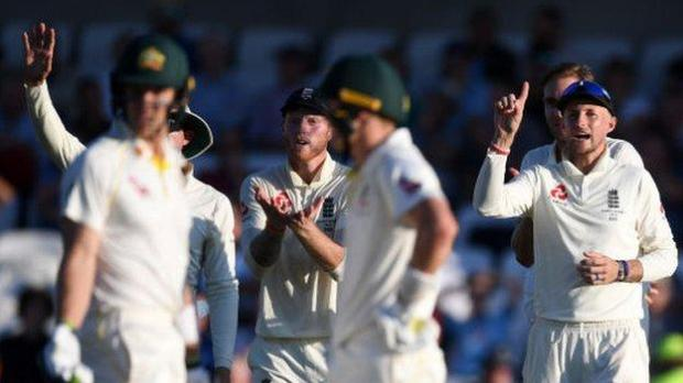 Tim Paine (out of focus) looks on as Joe Root and England team gesture 'out' with a raised finger