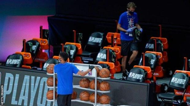 Workers remove items from the Milwaukee Bucks' bench area after they boycott an NBA play-off game