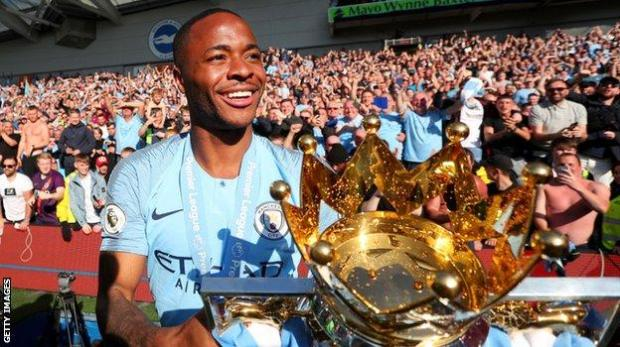 Raheem Sterling with the Premier League trophy after Manchester City's title win in 2018-19