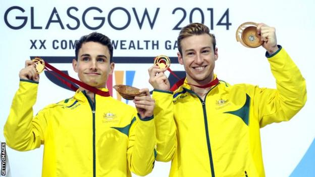 Australian divers Domonic Bedggood (left) and Matthew Mitcham (right) on the podium holding up their medals at the 2014 Glasgow Commonwealth Games