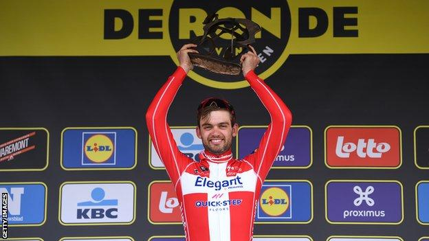 Denmark's Kasper Asgreen holds up the Tour of Flanders trophy on the podium