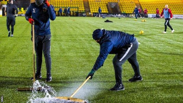 Grounds people try to clear the Livingston pitch of water