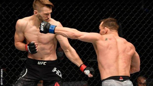 Michael Chandler punches Dan Hooker during his win at UFC 257
