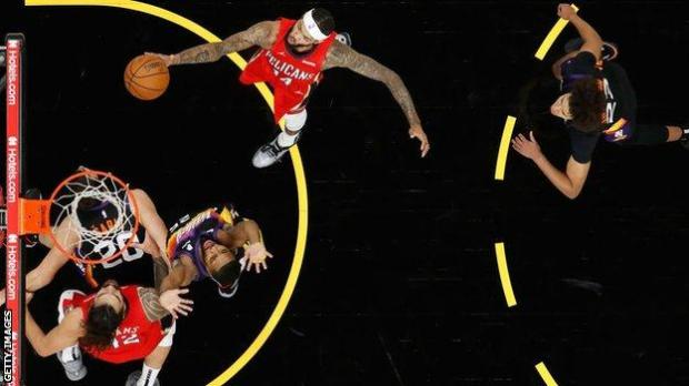 A New Orleans Pelicans player lays a shot up