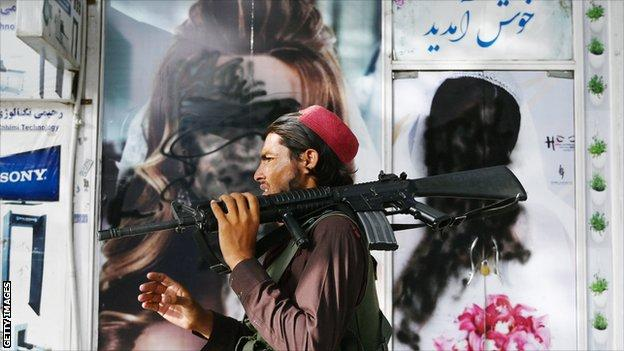A Taliban fighter walks past a beauty salon with images of women defaced using spray paint in Shar-e-Naw in Kabul on August 18, 2021