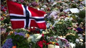 A Norwegian flag blows in the wind surrounded by flowers and candles outside the Oslo cathedral on July 26, 2011