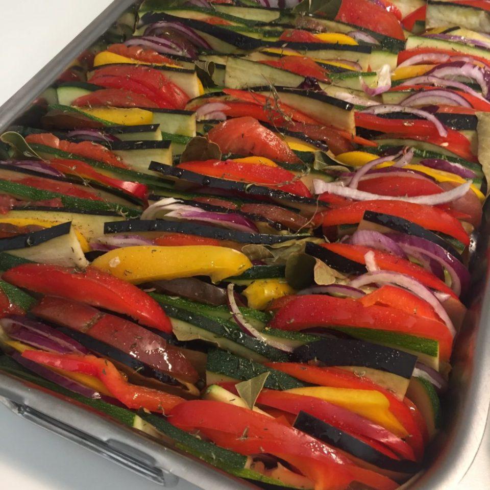 Tiens de légumes, courgettes aubergines oignons rouges plusieurs variétés de tomates, poivrons rouges et poivrons jaunes