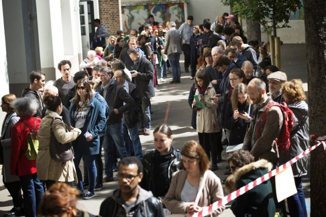Voters queue to cast their votes in the ongoing French presidential election