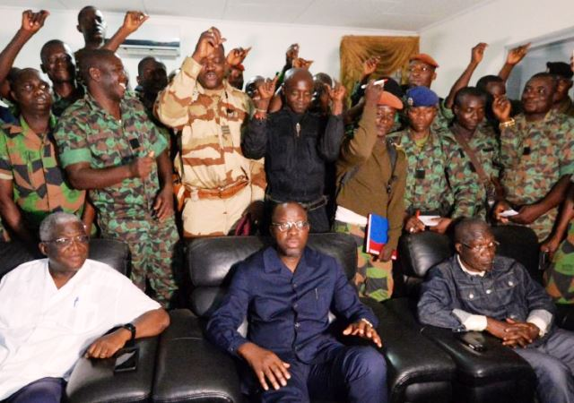 A delegation of mutinous Ivorian soldiers stand behind Defence Minister Alain-Richard Donwahi. Photo Credit: Yahoo