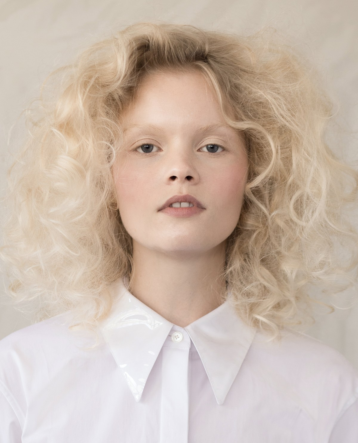 Blond model wearing a white Helmut Lang button-up shirt
